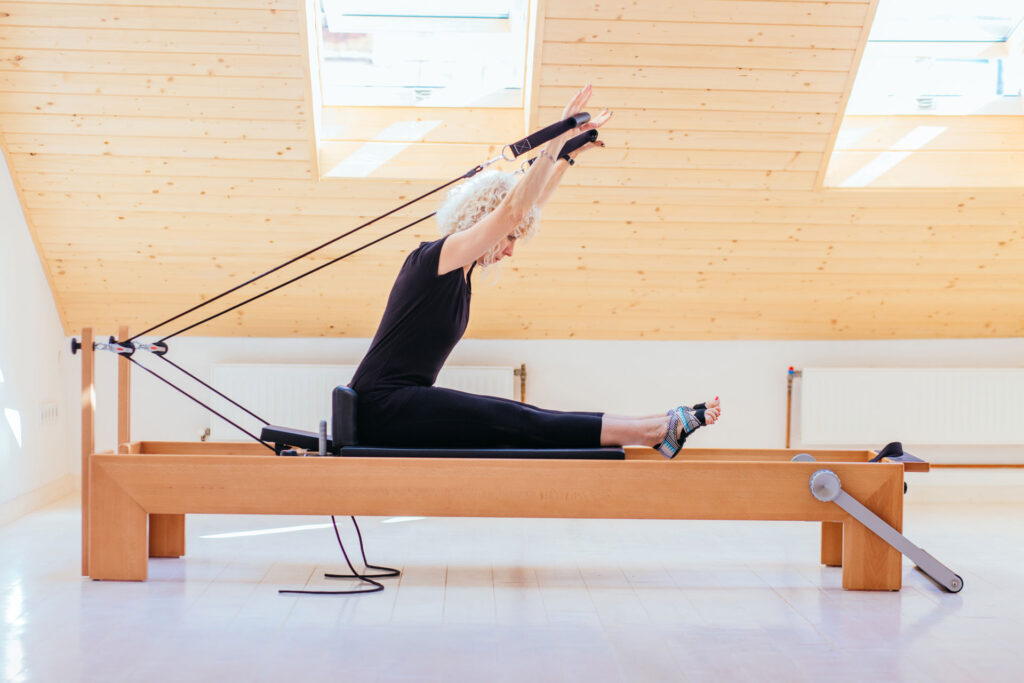 Woman doing reformer Pilates at home